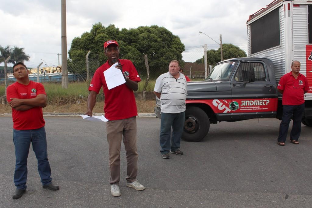 Ao microfone, o secretário de Comunicação, Benedito Irineu, mostra comunicado de greve e conversa com trabalhadores