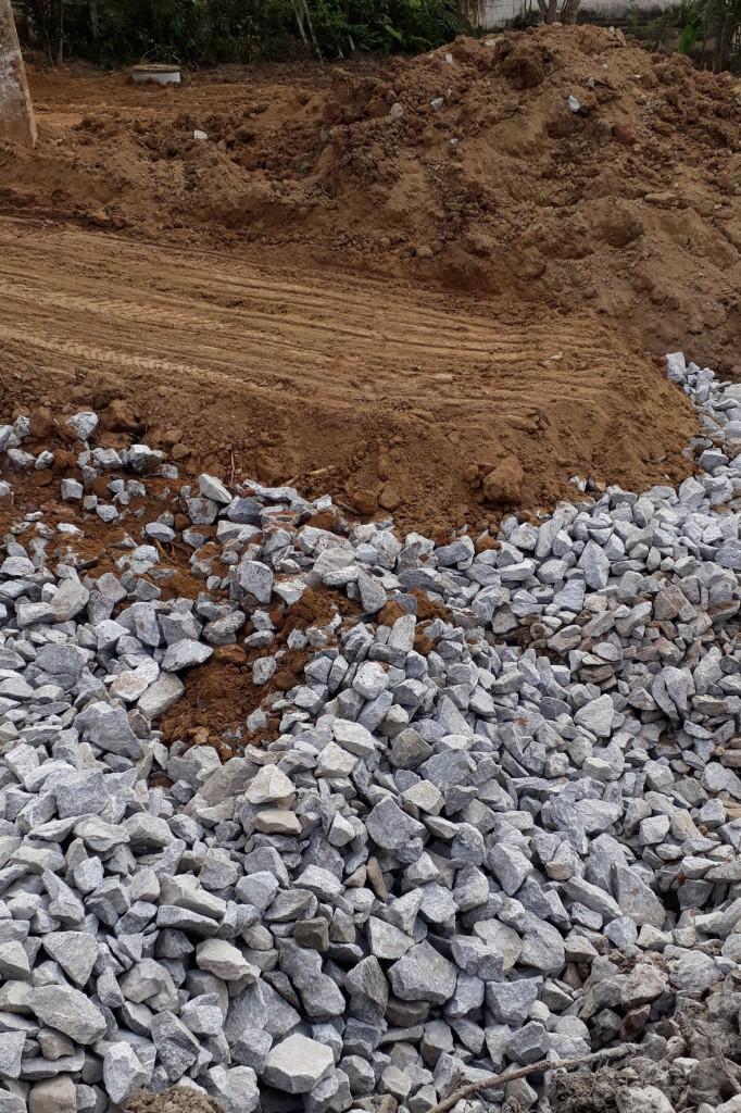 No solo úmido, foram jogados caminhões de pedra para permitir o aterramento