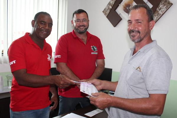 Valdir e o presidente Herivelto Vela entregam cheque de pagamento a Raimundo Nogueira, que ficou 13 anos exposto às más condições de trabalho